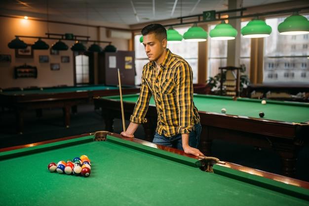 Mężczyzna gracz w bilard z cue przy zielonym stole z kolorowymi kulkami