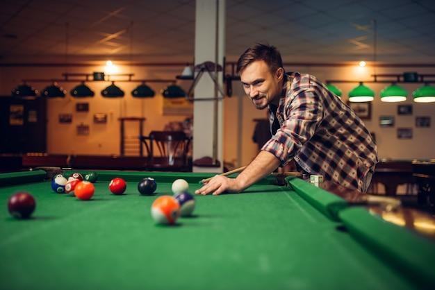 Mężczyzna gracz w bilard z kijem przy stole