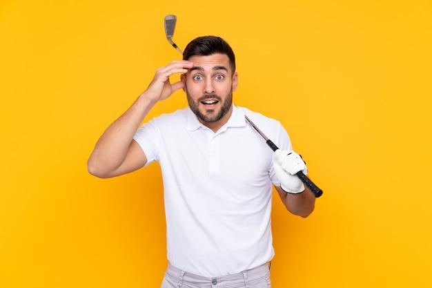 Mężczyzna gracz w golfa na pojedyncze żółte ściany z zaskoczenia i szoku wyraz twarzy