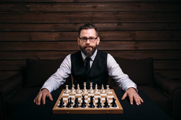 Mężczyzna gracz w okularach siedzi przeciwko szachownicy z zestawem sztuk.