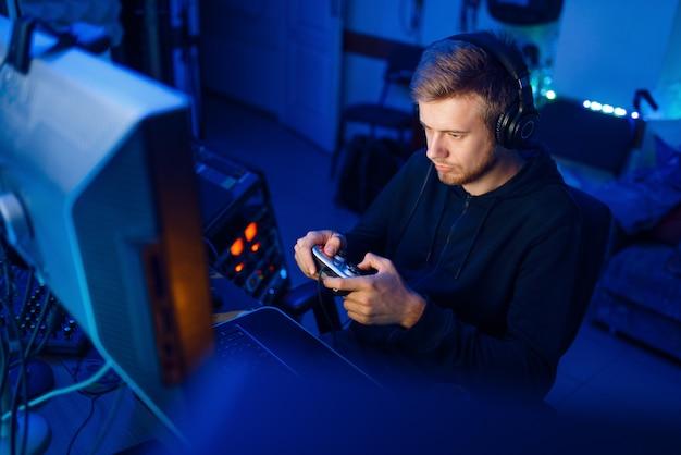 Mężczyzna gracz w słuchawkach trzyma joystick i gra w gry wideo na konsoli lub komputerze stacjonarnym, styl życia gier, cybersport. gracz w gry komputerowe w swoim pokoju z neonem, streamer