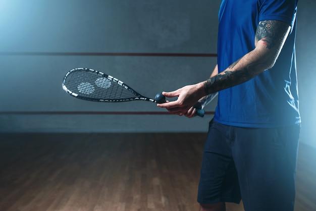 Mężczyzna gracz w squasha szkolenia na korcie kryty