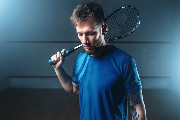 Mężczyzna gracz w squasha z rakietą, kryty kort treningowy