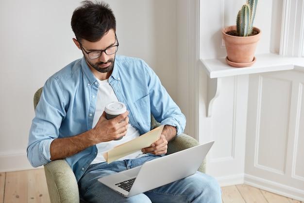 Mężczyzna grafik ogląda film instruktażowy o kreatywnych pomysłach na przenośnym laptopie, czyta wiadomości biznesowe, trzyma papier i kawę na wynos, pracuje jako wolny strzelec z domu, siedzi w fotelu