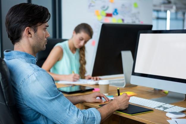 Mężczyzna grafik przy biurku przy użyciu tabletu graficznego