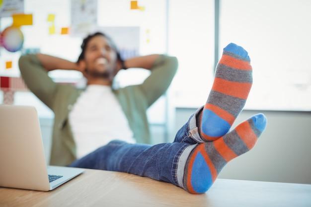 Mężczyzna grafik relaks z nogami przy biurku