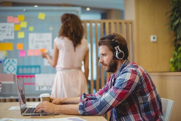 Mężczyzna grafik słucha piosenki podczas korzystania z laptopa
