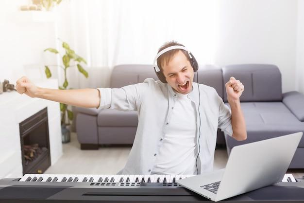 Mężczyzna grający muzykę z fortepianem i laptopem