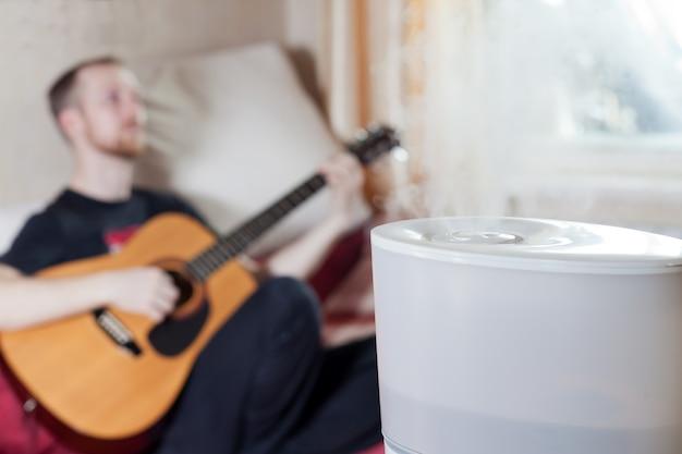 Mężczyzna grający na gitarze na blured tle nawilżacza