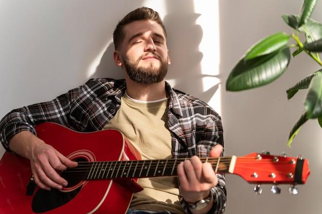 Mężczyzna grający na gitarze średni strzał