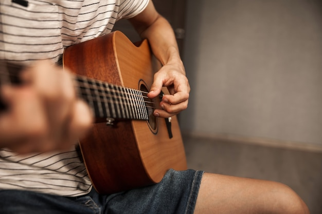 Mężczyzna grający na gitarze w domu, z bliska zdjęcie rąk