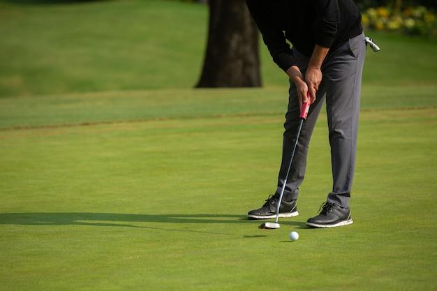 Mężczyzna grający w golfa, putting green