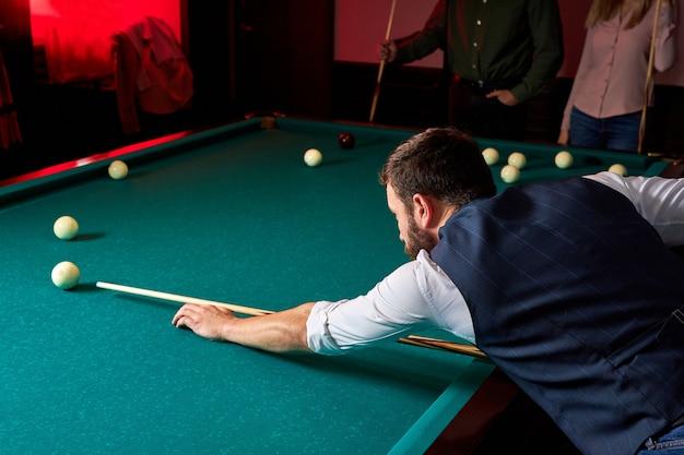 Mężczyzna grający w snookera, podszewka, aby uderzyć piłkę na stole bilardowym. po pracy przyjemna rozrywka w barze