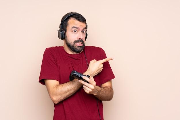 Mężczyzna grający z kontrolerem gier wideo nad izolowaną ścianą przestraszony i wskazujący na bok