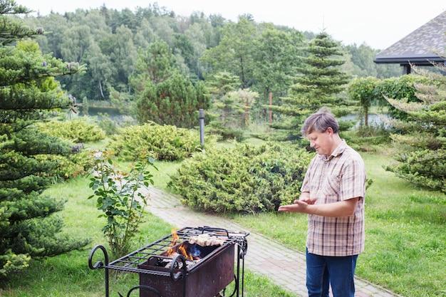 Mężczyzna grilluje latem w ogrodzie