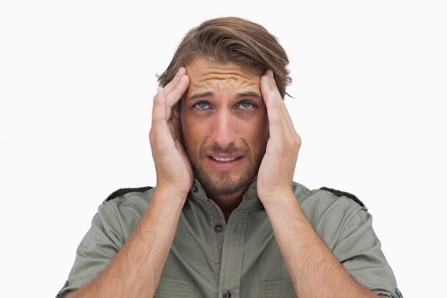 Mężczyzna grymasy z bólem głowy i patrząc w górę