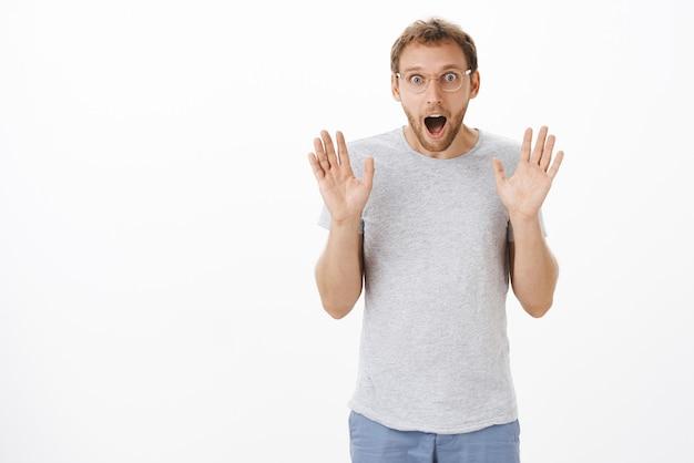 Mężczyzna gubi mowę od ekscytujących wiadomości, unosząc dłonie w kapitulacji, opuszczając szczękę i wpatrując się w rozbawiony i zdumiony, wstrzymując oddech, zachwycony podczas pozowania