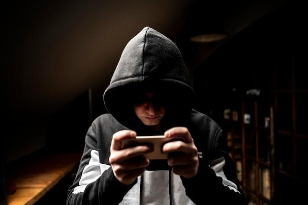 Mężczyzna haker w kapturze za pomocą telefonu komórkowego, kradzież danych osobowych