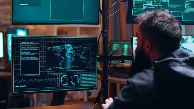 Mężczyzna haker wpisujący na klawiaturze niebezpieczne złośliwe oprogramowanie do kradzieży z serwera rządowego.
