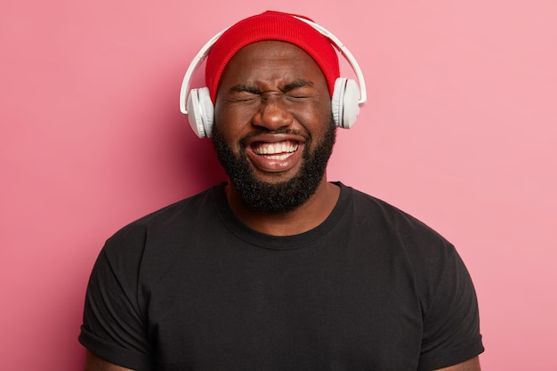 Mężczyzna hipster słucha muzyki w słuchawkach bezprzewodowych na białym tle
