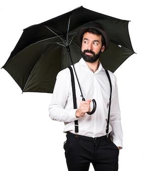 Mężczyzna hipster z brodą trzyma parasol