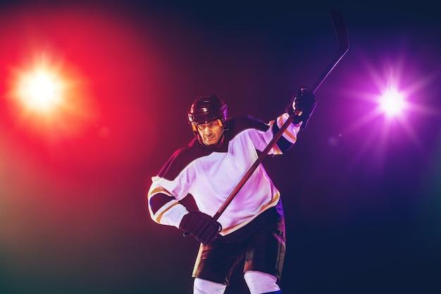 Mężczyzna hokeista z kijem na boisku i ciemnej neonowej ścianie