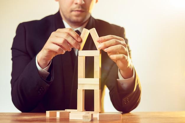 Mężczyzna i drewniane kostki na stole. koncepcja zarządzania