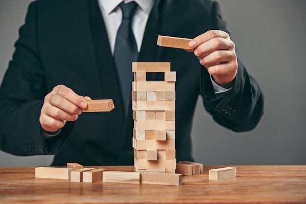 Mężczyzna i drewniane sześciany na stole. koncepcja zarządzania
