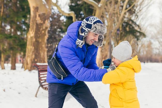 Mężczyzna i dziecko bawią się zimą w parku, ojciec i syn bawią się razem