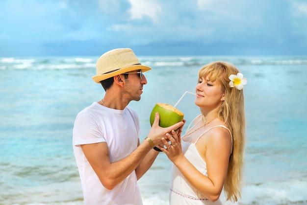 Mężczyzna i dziewczyna na plaży piją kokos.