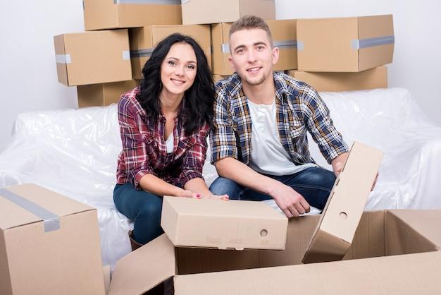 Mężczyzna i dziewczyna siedzą w domu i rozkładają pudełko.