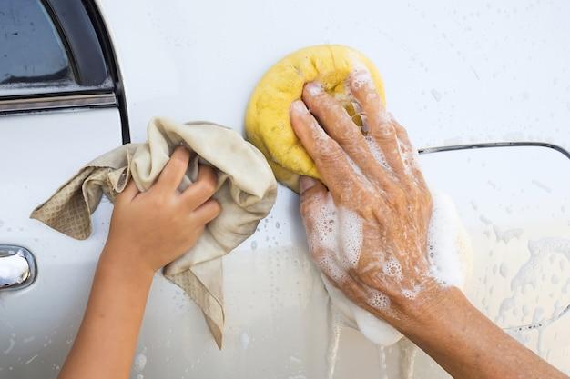 Mężczyzna i dziewczyna używa żółtą gąbkę myje samochód.