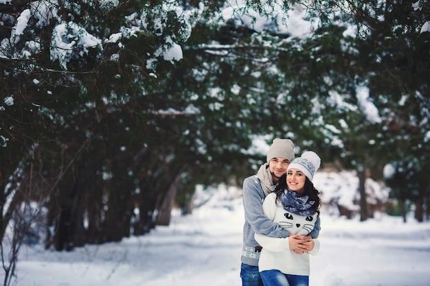 Mężczyzna i dziewczyna w sweterkach przytulanie w parku zimą. młoda para zakochanych, zabawy na zimowym spacerze