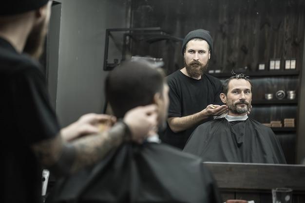 Mężczyzna i fryzjer odbity w lustrze w salonie fryzjerskim. fryzjer nosi czarną koszulkę z czapką i ma grzebień do włosów