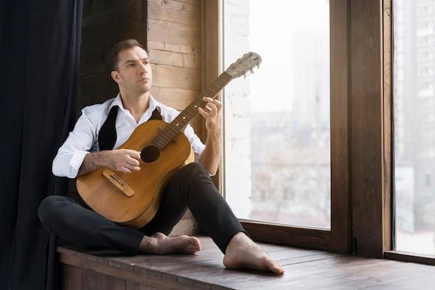 Mężczyzna i gitara obok okien