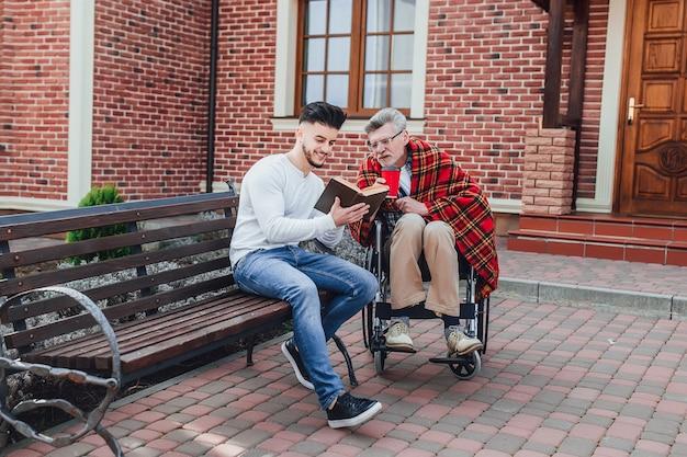 Mężczyzna i jego ojciec w pobliżu domu opieki, czytają książkę