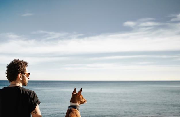 Mężczyzna i jego pies na plaży, podziwiając morze