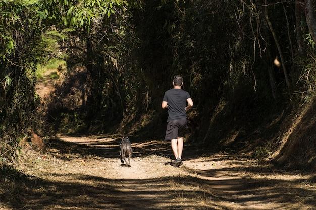 Mężczyzna i jego pies pitbulla biegnący po polnej drodze on i pitbull ćwiczą