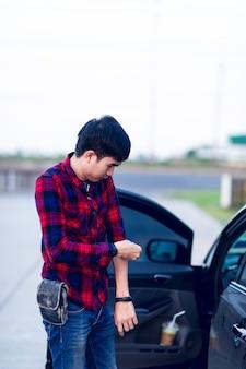 Mężczyzna i jego samochód stali na poboczu drogi.