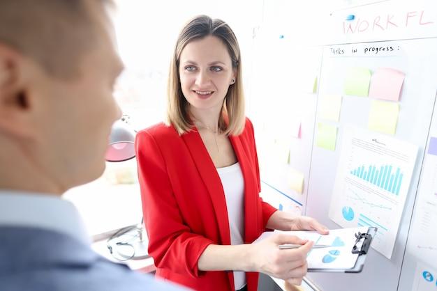 Mężczyzna i kobieta, badanie danych na wykresie w pobliżu tablicy