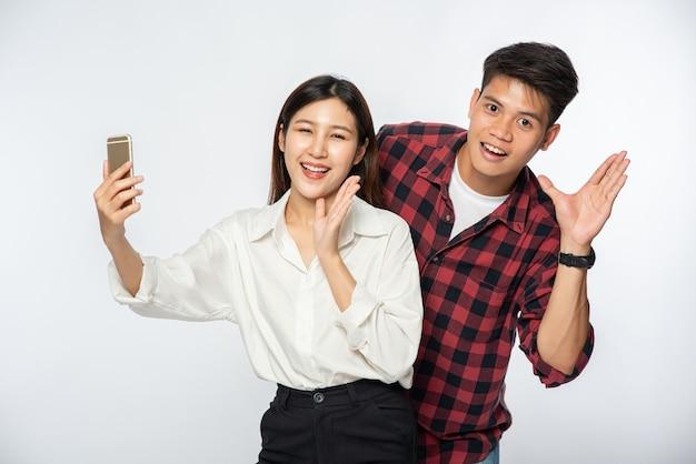 Mężczyzna i kobieta bawią się selfie ze swoich smartfonów