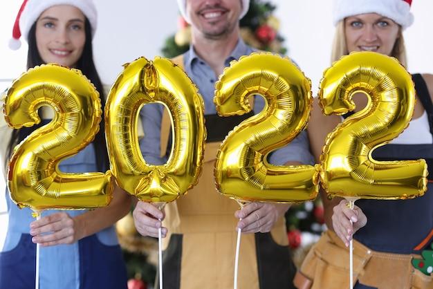 Mężczyzna i kobieta budowniczych w czapkach świętego mikołaja, trzymających złote balony z numerami 2022 zbliżenie. koncepcja firmowych imprez noworocznych
