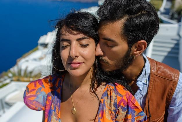 Mężczyzna i kobieta całują się na skale skaros na wyspie santorini. wieś imerovigli, etniczny cygan. ona jest izraelką.