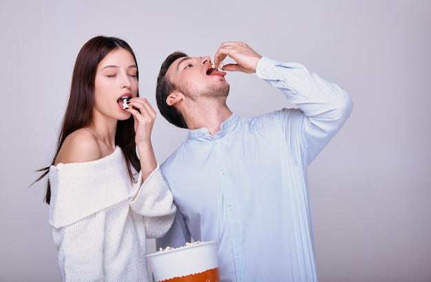 Mężczyzna i kobieta chętnie jedzą popcorn.