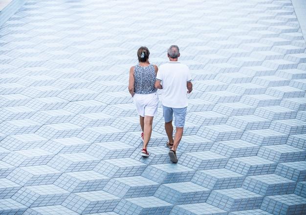 Mężczyzna i kobieta chodzą zrelaksowani, para idzie przez samotną przestrzeń, minimalistyczna koncepcja, samotność, relaks, spokój, rozmowa lato, zachód słońca, stałość