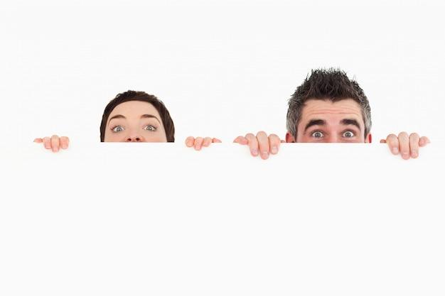 Mężczyzna i kobieta chowa się za białą deskę z pokoju dla kopii sp