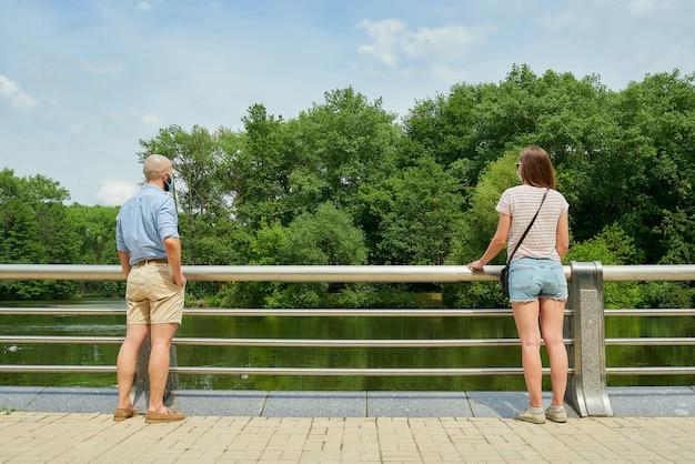 Mężczyzna i kobieta cieszą się widokiem na rzekę, zachowując odległość kilku metrów, aby uniknąć rozprzestrzeniania się koronawirusa.