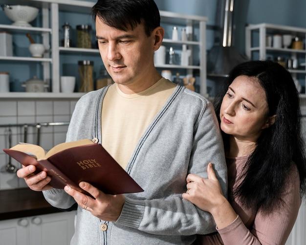 Mężczyzna i kobieta czytają biblię w kuchni