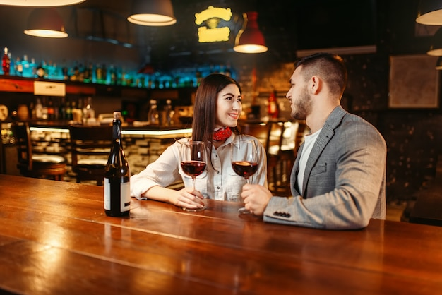 Mężczyzna i kobieta flirtują w barze, romantyczny wieczór, para przy drewnianym blacie. miłośnicy spędzają czas w pubie, mąż i żona relaksują się razem w nocnym klubie