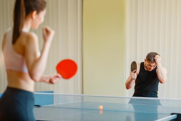 Mężczyzna i kobieta gra w ping ponga w pomieszczeniu